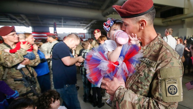 Sean Smith, a paratrooper with the 1st Brigade Combat Team, 82nd Airborne Division, kisses his daughter Olivia Rose Smith, 10 months. Credit: Reuters