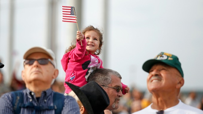 A young girl waves a US flag as troops return home to Pope Army Airfield in Fort Bragg, North Carolina. Credit: Reuters