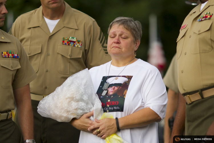 "Cathy Wells, the mother of Marine Lance Cpl. Squire K. ""Skip"" Wells, who was one of the five military servicemen slain last week in Chattanooga in a domestic terror attack, is escorted by members of the U.S. military at her son's vigil at Sprayberry High School in Marietta, Georgia July 21, 2015.  REUTERS/Chris Aluka Berry"