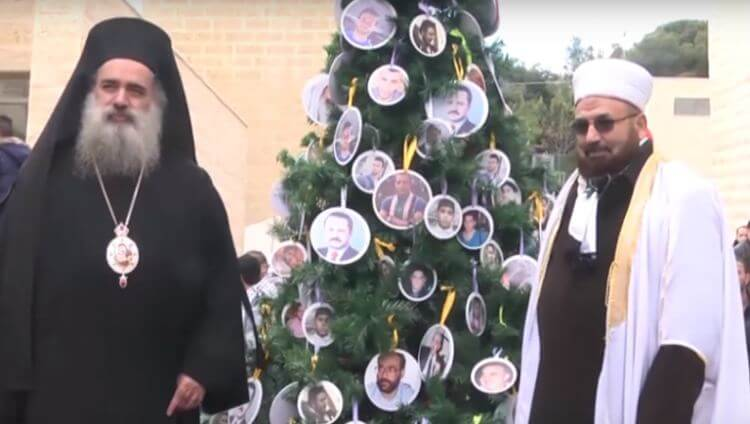 The Mufti of Bethlehem stands next to the Christmas tree of Al Quds University
