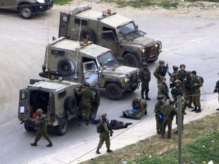 IDF soldiers guard the body of the terrorist who stabbed a pregnant Jewish woman near Tekoa today