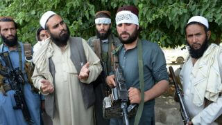 Afghan Taliban militants stand with residents as they took to the street to celebrate ceasefire on the second day of Eid in the outskirts of Jalalabad on June 16,2018. - Taliban fighters and Afghan security forces hugged and took selfies with each other in restive eastern Afghanistan on June 16, as an unprecedented ceasefire in the war-torn country held for the second day of Eid.