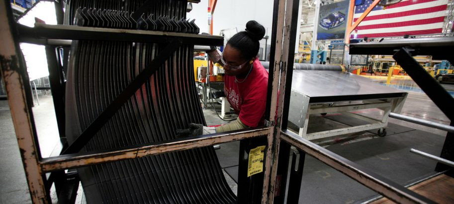 A Fiat Chrysler Automobiles worker handles a part that came off the press at the FCA Sterling Stamping Plant August 26, 2016 in Sterling Heights, Michigan.