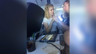 A young girl helps communicate with a deaf and blind man on an airplane.