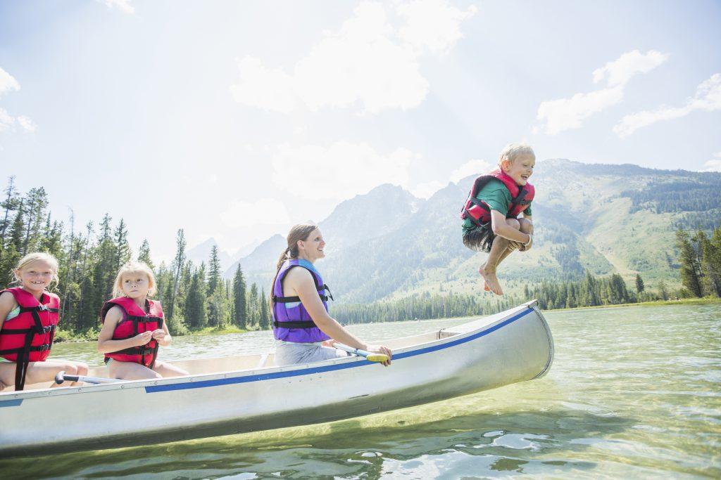 Caucasian boy jumping from canoe into lake