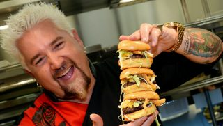 LAS VEGAS, NV - APRIL 04: Chef and television personality Guy Fieri holds hamburgers in the kitchen during a welcome event for Guy Fieri's Vegas Kitchen & Bar at The Quad Resort & Casino on April 4, 2014 in Las Vegas, Nevada. The restaurant opens on April 17.