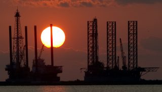 The sun sets behind two under construction offshore oil platform rigs in Port Fourchon, Louisiana, June 14, 2010.