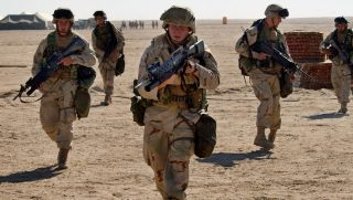 NEAR IRAQI BORDER, KUWAIT - FEBRUARY 1: U.S. Marines from 3rd Battallion 1st Marine Division practice squad rushes February 1, 2003 at Living Support Area 7 near the Iraqi border in northern Kuwait. The U.S. military continues a buildup of its forces in the region ahead of possible conflict in Iraq with upwards of 150,000 troops expected by mid-February.
