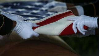 A military honor guard folds the the American Flag a top the casket