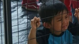 Photo of young boy inside a cage constructed for a protest in Dallas, crying when he sees his mother.