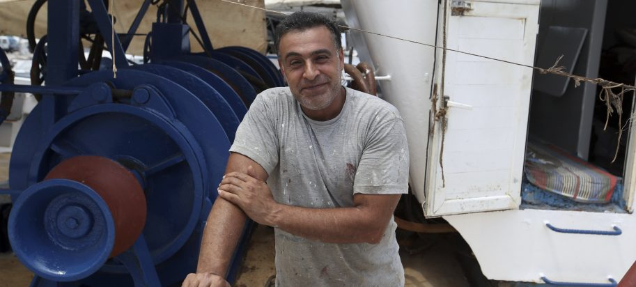 Egyptian fisherman Halil Tawefik poses on his fishing boat in Rafina port, east of Athens, Wednesday, July 25, 2018. Tawefik says the cries for help pierced the thick, choking smoke as his fishing boat plucked young and old from the sea where they sought refuge from the flames that tore through the seaside report of Rafina.