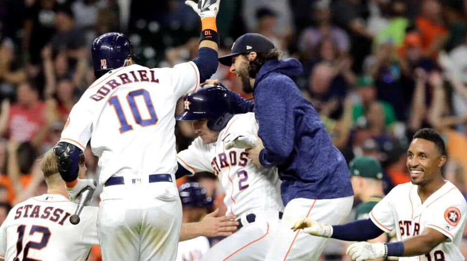 Houston Astros' Alex Bregman (2) celebrates with teammates after hitting a ground ball to Oakland Athletics catcher Jonathan Lucroy to score Kyle Tucker during the 11th inning of a baseball game Tuesday, July 10, 2018, in Houston. The Astros won 6-5.