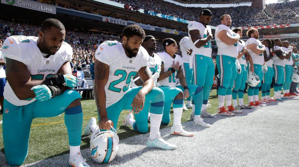Members of the Miami Dolphins take a knee to protest the national anthem during a 2017 game