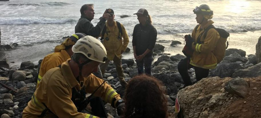 In this Friday, July 13, 2018, photo posted on the Monterey County, Calif., Sheriff's Office Twitter feed, authorities tend to Angela Hernandez, foreground center, after she was rescued, in Morro Bay, Calif. Authorities say a couple on a camping trip came upon Hernandez, from Oregon, who had been missing since July 6, after her car went over a cliff in coastal California. (