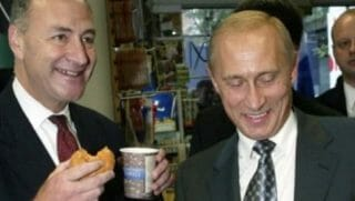 Chuck Schumer, left, holding coffee and a donut. Putin, on the right, is laughing.