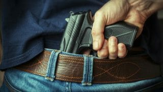A man reaches for his concealed firearm