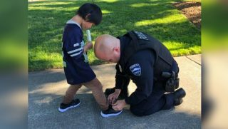 A cop kneels down to help put a new pair of shoes on a little boy after giving him a Popsicle.
