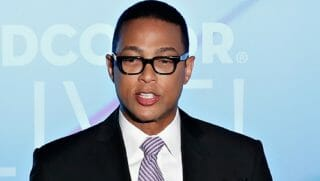 Don Lemon standing, speaking into a microphone