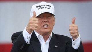 "Donald Trump flashes two thumbs up while wearing a ""Make America Great Again"" baseball cap."
