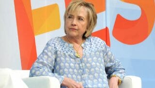 Hillary Clinton scowling to her left wearing what looks like a flowered hospital gown.