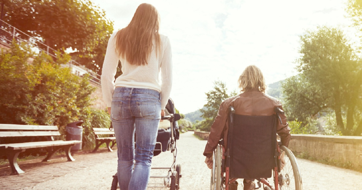 A woman pushes a stroller while a man rolls next to her in a wheelchair.
