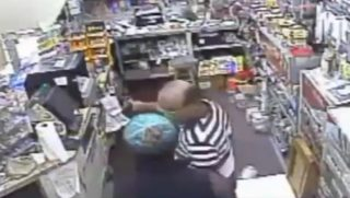 An armed robber takes cash from a convenience store in Florida.