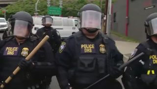Police stand in riot gear outside the ICE headquarters in Portland, Oregon