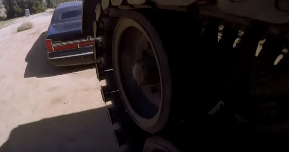 A tank's treads about to strike a black limousine.