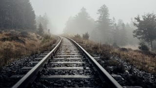 train tracks leading off into the fog