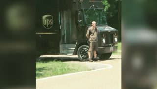 UPS driver stands outside delivery truck on the side of the road