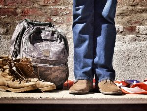 National Hire a Veteran Day: Man standing next to his military backpack, boots, and an American flag