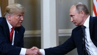 Russian President Vladimir Putin (R) and US President Donald Trump shake hands before a meeting in Helsinki, on July 16, 2018