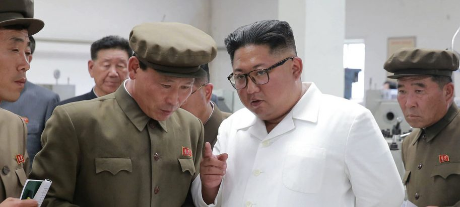 Kim Jong Un, center, speaks during a visit to a machine factory.