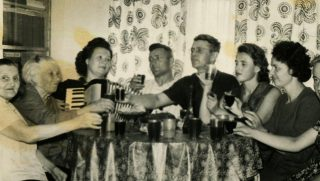 Old black and white photograph of people sitting around the table