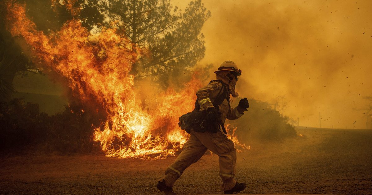 FILE - In this Tuesday, July 31, 2018, file photo, a firefighter runs while trying to save a home as a wildfire tears through Lakeport, Calif. The residence eventually burned. Authorities say a rapidly expanding Northern California wildfire burning over an area the size of Los Angeles has become the state's largest blaze in recorded history. It's the second year in a row that California has recorded the state's largest wildfire.