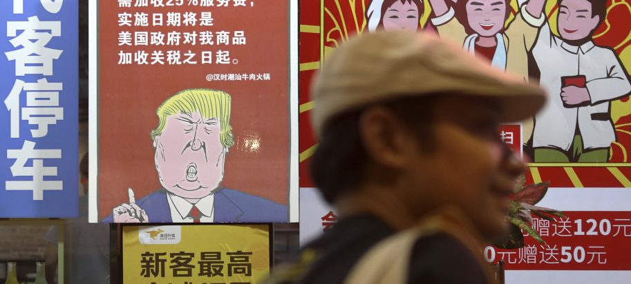 a man walks by a poster depicting a mural of U.S. President Donald Trump stating that all American costumers will be charged 25 percent more than others starting from the day president Trump started the trade war against China, on display outside a restaurant in Guangzhou in south China's Guangdong province.