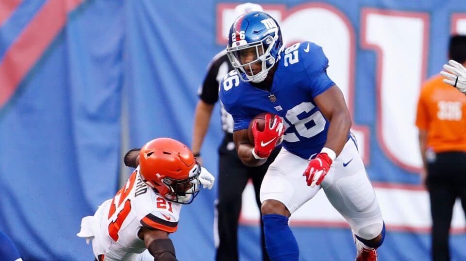 Giants running back Saquan Barkley dodges a defender during his preseason debut