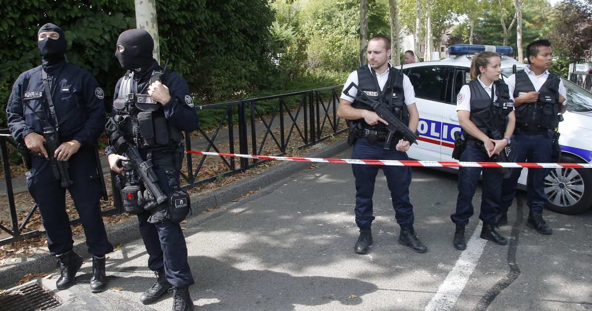 French hooded police officers guard the area with other police officers after a knife attack Thursday, Aug. 23, 2018 in Trappes, west of Paris. A man flagged by French authorities as a suspected radical killed his mother and sister and seriously injured another woman in a knife attack.
