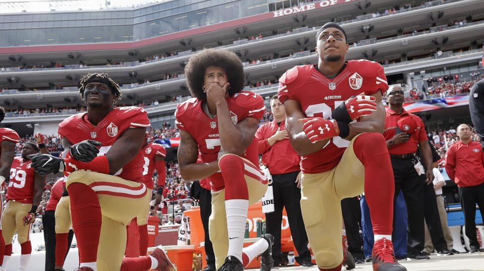 In this Oct. 2, 2016 file photo, from left, San Francisco 49ers outside linebacker Eli Harold, quarterback Colin Kaepernick and safety Eric Reid kneel during the national anthem before a game against the Dallas Cowboys in Santa Clara, California.