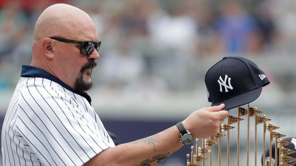 Former New York Yankees pitcher David Wells puts his hat on the 1998 World Series trophy during a ceremony honoring the team prior to a baseball game between the New York Yankees and the Toronto Blue Jays Saturday in New York.