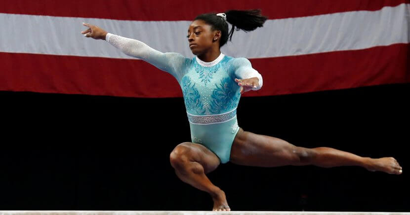 Simone Biles crouche on one foot on the balance beam.