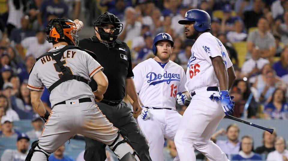 San Francisco Giants catcher Nick Hundley, left, reacts to being shoved by Los Angeles Dodgers' Yasiel Puig, right, as they argue while home plate umpire Eric Cooper, second from left, gets between them and Max Muncy runs in during the seventh inning of a baseball game, Tuesday, Aug. 14, 2018, in Los Angeles.