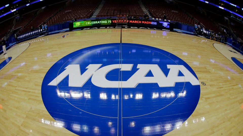 In this March 21, 2013, file photo, taken with a fisheye lens, the NCAA logo is displayed on the court during the NCAA college basketball tournament in Philadelphia.