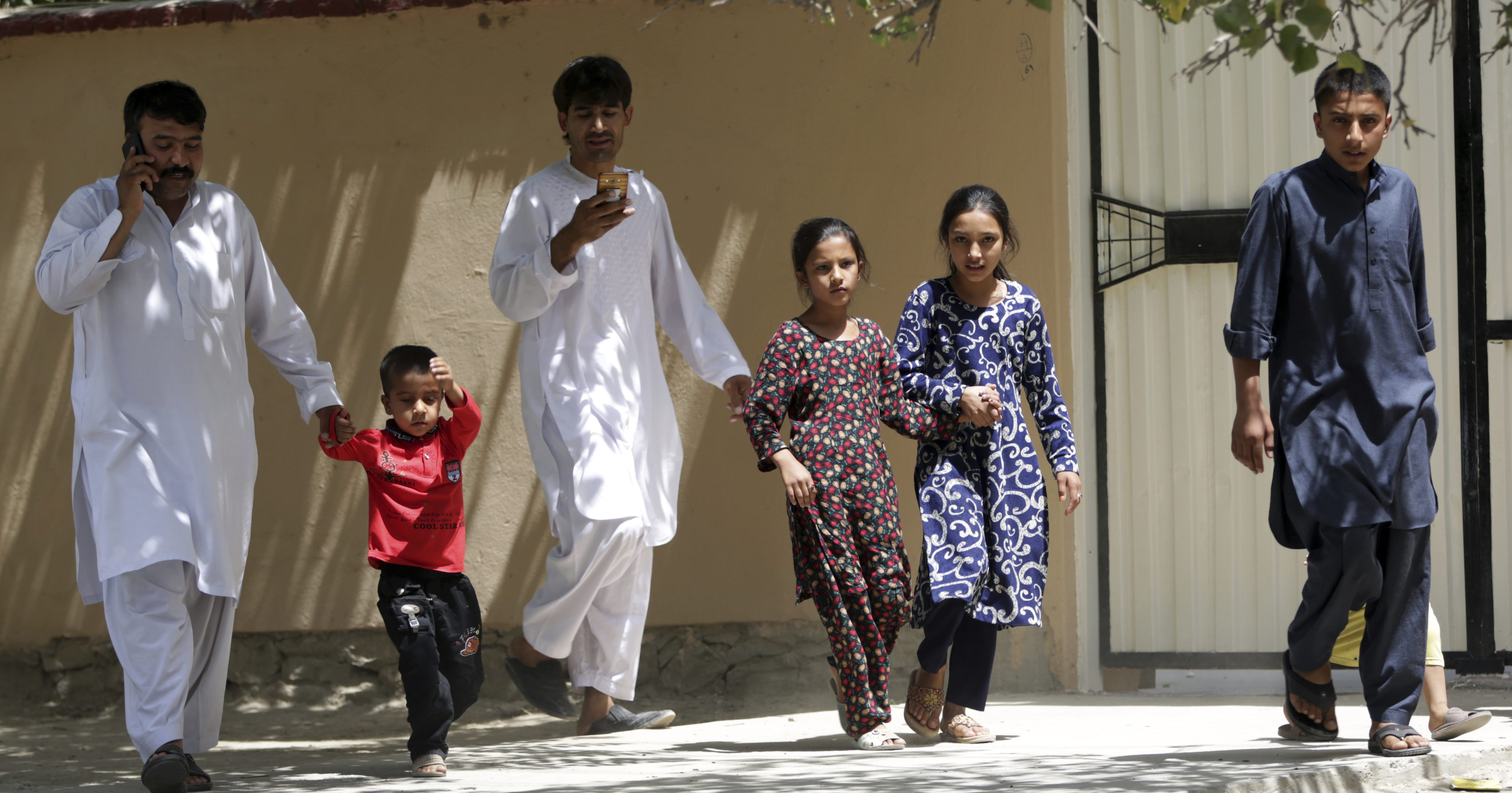 Families leave their houses during a nearby clash between insurgents and security forces in Kabul, Afghanistan, Aug. 16, 2018.