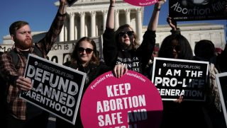 Pro-life activists try to block the signs of pro-choice activists in front of the the U.S. Supreme Court during the 2018 March for Life January 19, 2018 in Washington, DC.