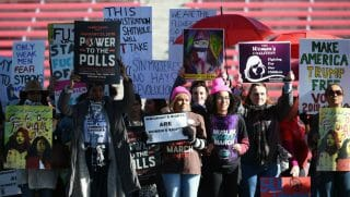 Attendees hold signs onstage during the Women's March 'Power to the Polls' voter registration tour launch at Sam Boyd Stadium on January 21, 2018 in Las Vegas, Nevada.