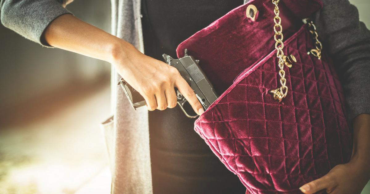 Woman putting gun in purse