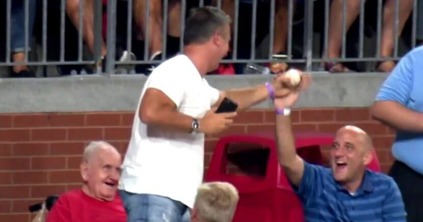 A fan is congratulated after making a one-handed catch of a fly ball while talking on the phone during the Phillies-Red Sox game.