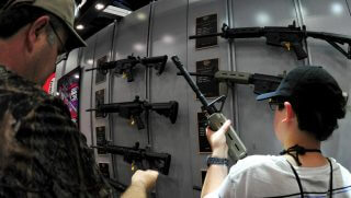 A father and his son look at Colt semiautomatic rifles at the NRA Convention on May 4, 2013 in Houston.