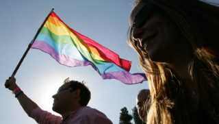 A rainbow flag is held aloft.